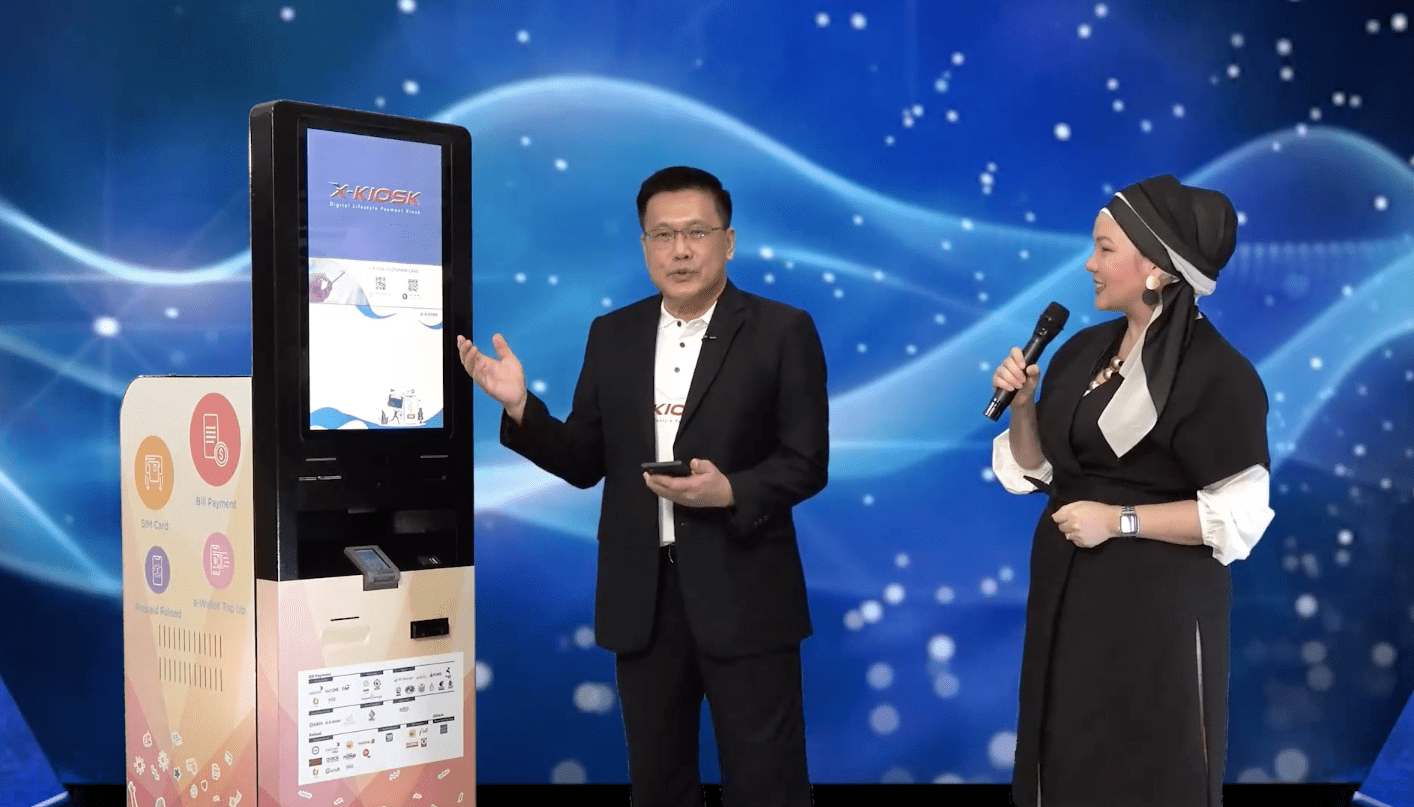 OpenSys CEO Eric Lim (Left) performing the first prepaid reload transaction with the Touch 'n Go eWallet on the X-Kiosk
