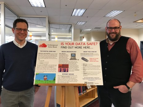 "Figure 1: John Durno and Matt Huculak in front of the ""Is Your Data Safe"" poster"