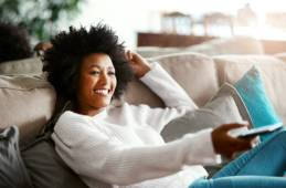 Shot of a young woman relaxing on the sofa at home and watching tv