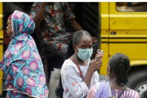 A woman wearing a face mask walks nearby the Central Mosque in Lagos, Nigeria, Friday, March 20, 2020. The government banned all religious activities for four weeks following confirmation of coronavirus cases in the country.  (AP Photo/Sunday Alamba)