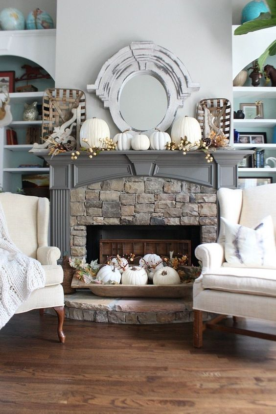 a fireplace styled with white pumpkins, berries, greenery and feathers and an additional arrangement in a dough bowl