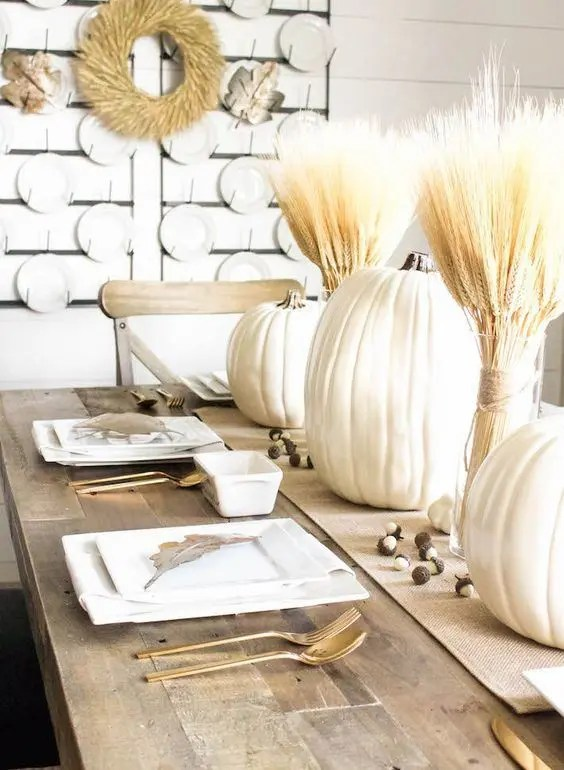a white fall tablescape with white pumpkins, wheat bundles, acorns, white square plates and gold cutlery