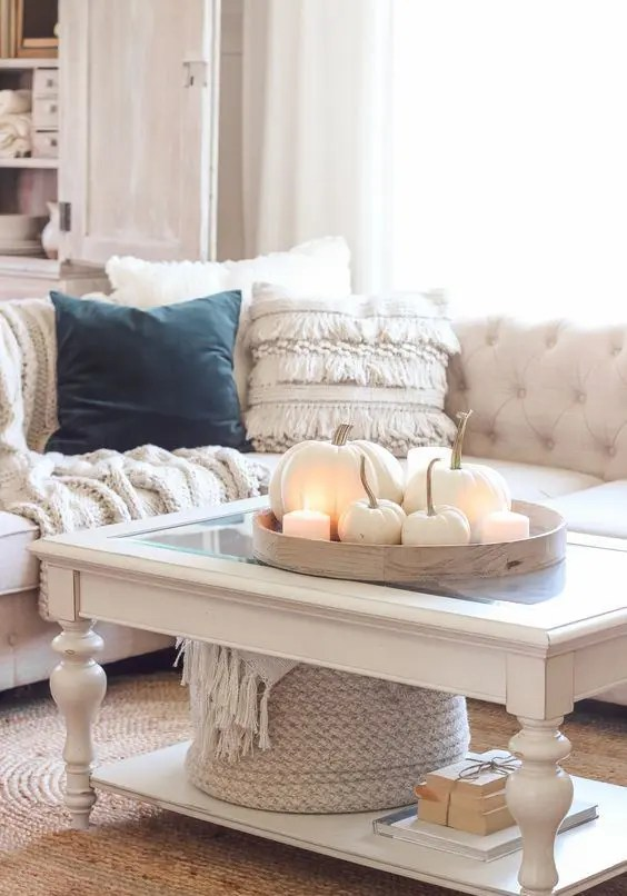 cozy neutral fall decor - a tray with white pumpkins and pillar candles, a white blanket in a basket