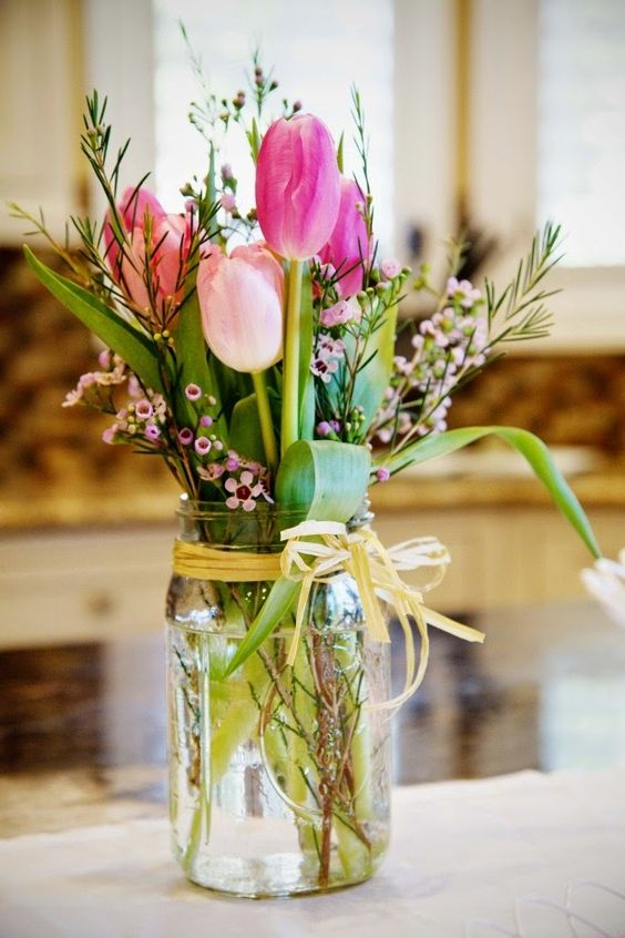 a beautiful Easter flower arrangement with pink tulips and other blooms plus greenery is a simple and cool rustic idea