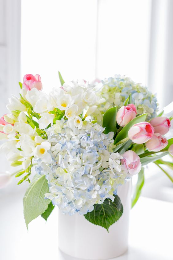 a beautiful and very simple spring flower arrangement of hydrangeas, daffodils, tulips in pastel shades is wow
