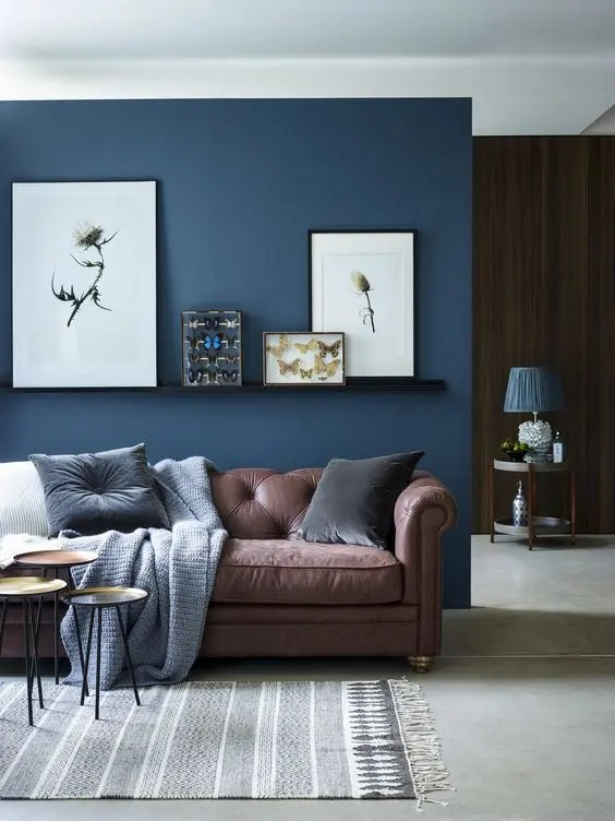 26 Cool Brown And Blue Living Room Designs   DigsDigs chic seating area with a brown sofa and a navy accent wall and textiles