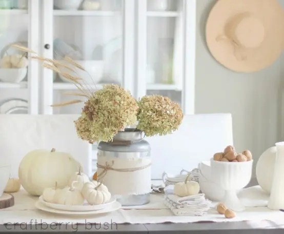 a white and neutral fall tablescape with a white table runner, white pumpkins, nuts in a bowl and neutrla hydrangeas for the fall
