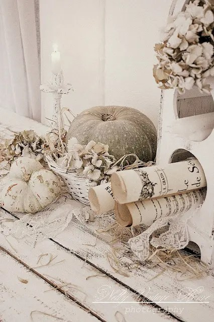 neutral shabby chic fall decor with white lace, dried leaves, vintage prints, neutral and painted pumpkins and candles