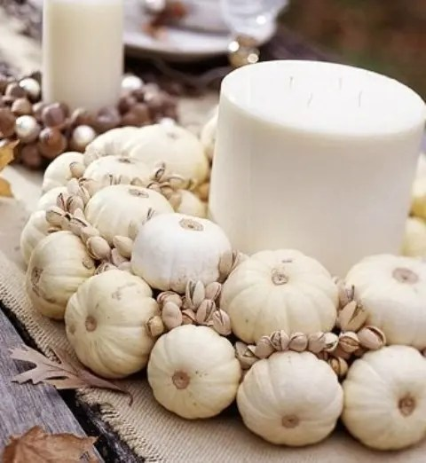 a white fall centerpiece of a giant pillar candle and white pumpkins and pistachios is a creative and all-natural idea
