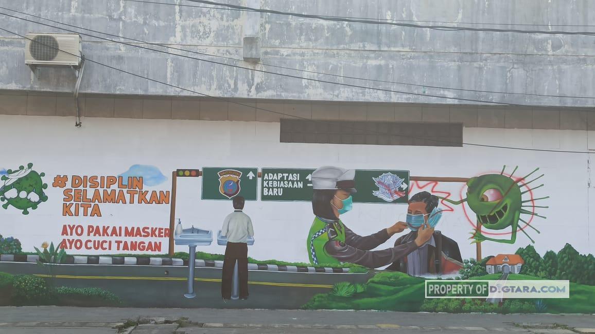 Gambar lukisan dinding karya Komunitas Mural Medan di dinding gedung sekitaran jalan rel Kreta Api