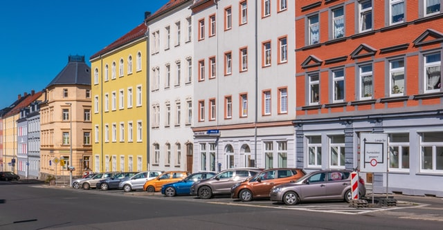 A residential district street with assorted-color cars parked along the street - How do I market my real estate listings