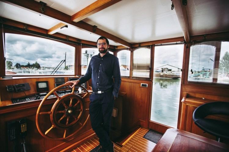 Max Gérard à la barre du Minerva, un luxmotor (bateau de transport d'origine hollandaise souvent aménagé en logement) de 30 mètres entièrement remis en état par les ateliers d'H2O. Prix de revente annoncé de cette péniche de luxe capable de naviguer en mer : 520 000 euros.