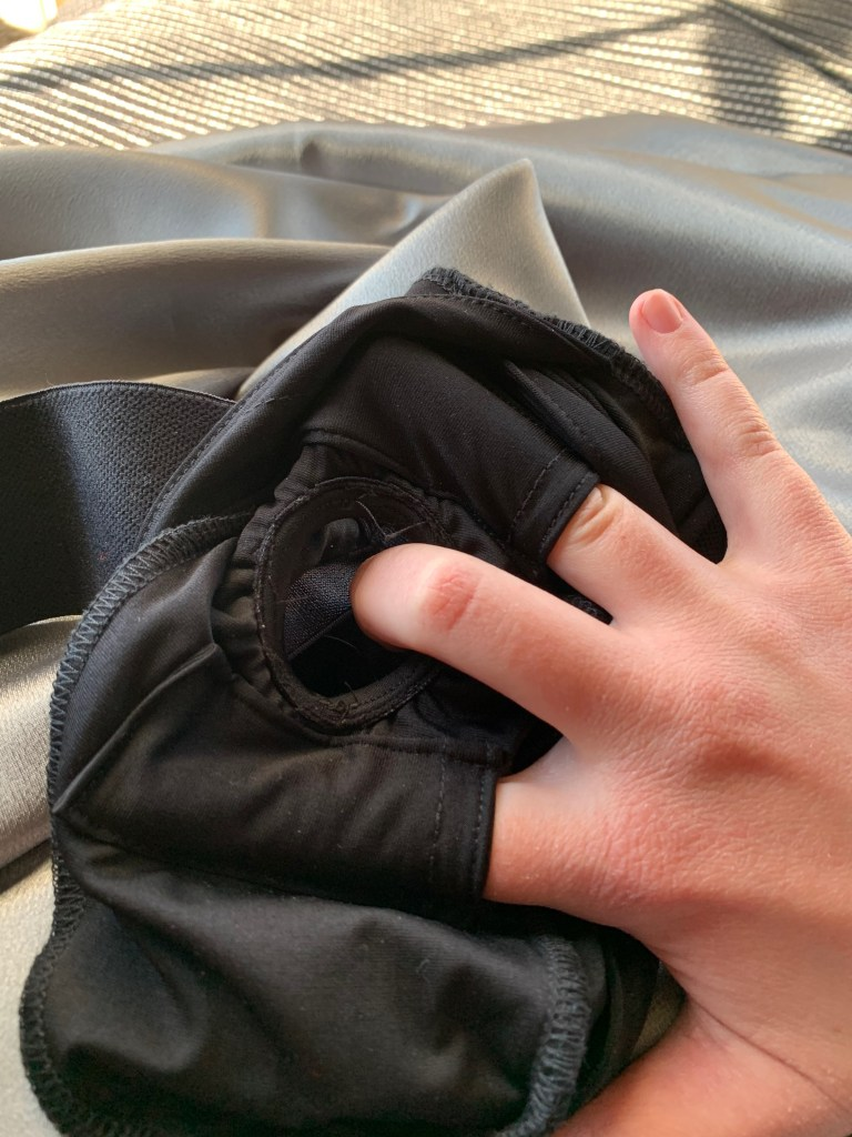Demonstrating placement of SpareParts Joque harness bullet pockets by placing a finger in both the top and bottom pockets.