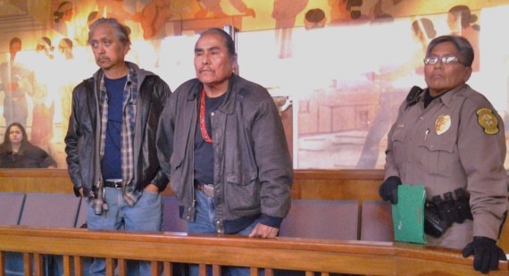 """Shiprock, N.M., community member Larry Emerson stands with Navajo Nation Shiprock Chapter President Duane """"Chili"""" Yazzie as he challenges the Navajo Council, which ordered the Navajo police to remove Yazzie from the Council chamber in Window Rock, Ariz., on Dec. 23, 2013. Photo by Marley Shebala"""
