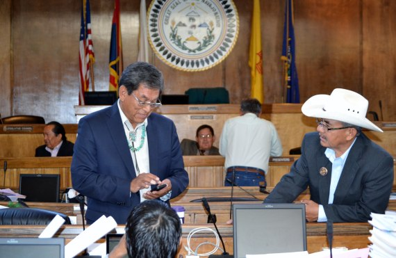 As the Navajo Council Naabik'iyati Committee wait for a quorum, Delegates Russell Begaye (holding cell phone), Nelson BeGaye (white hat) and Jonathan Nez visit in the Council chamber in Window Rock, Ariz., on July 17, 2014. In the background is Chief Legislative Counsel Levon Henry and Naabik'iyati Committee Chairperson Pro Temp LoRenzo Bates who is talking with Delegate George Apachito.  Photo by Marley Shebala. (Please provide proper photo credit when reusing photo.)
