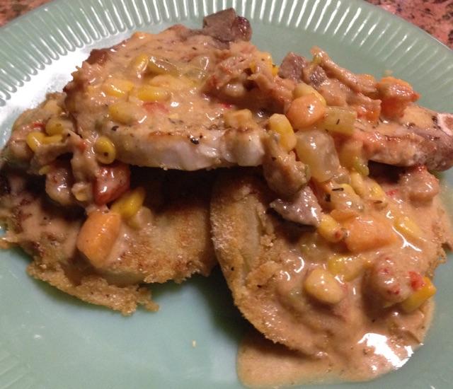 Seared Bone-In Pork Chop, Eggplant and covered in Spicy Corn-N-Crawfish Sauce