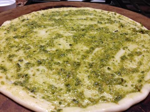 Pizza crust covered in pesto