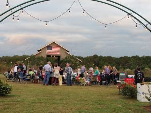 Weeks Bay Plantation barn with American Flag, lots of people waiting for concert www.diningwithmimi.com
