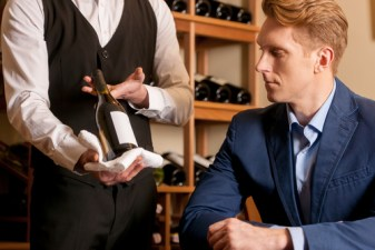 sommelier-showing-a-wine-bottle-to-customer