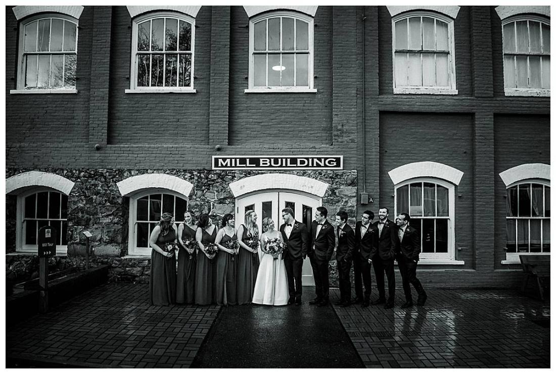 Wedding party group portrait taken outside the Thomas Kay Woolen Mill building.
