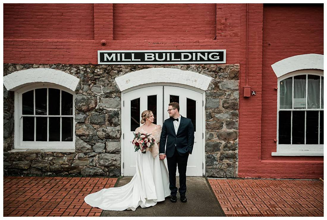 Bride and groom image standing outside the main doors of the Thomas Kay Woolen Mill building at the Willamette Heritage Center