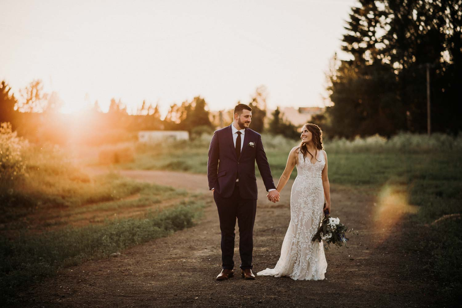 Golden hour bride and groom portrait holding hands taken in a field outside of the troutdale house by the Sandy river in Portland Oregon.
