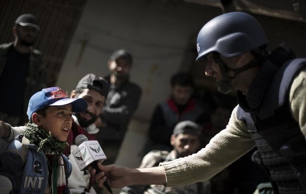 Abou Hussein interroge un petit Syrien, à Deir Ezzor le 19 février 2013 [Zac Baillie / AFP]