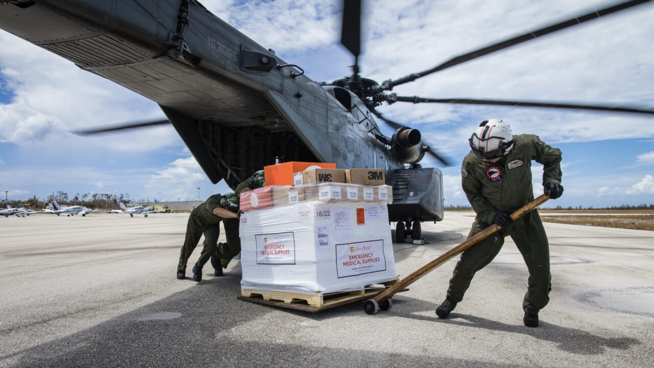 Workers unload medical supplies from a helicopter.