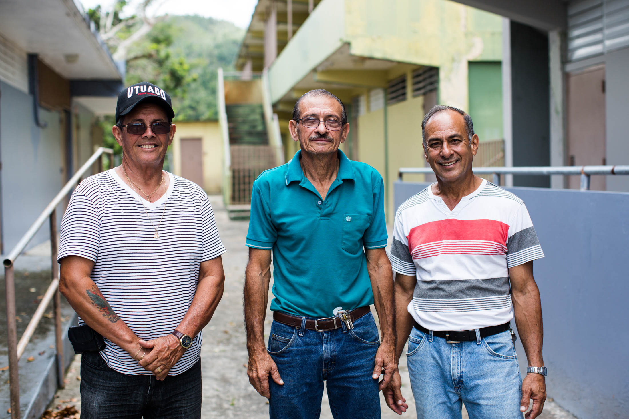 From left, William Reyes, Miguel Morales and Ivan Robles, of the community non-profit Acción Comunitaria del Viví, Inc., pose for a portrait at their home-base in Barrio Vivi Arriba, Utuado, P.R., on May 26, 2018. Inside the former public school, the group, funded by Direct Relief, opened a free laundry service for the two nearby communities who have been without power for over eight months. The entity, presided by Morales, serves as a community and aid center in the aftermath of hurricane Maria. Many of the residents of the mountainous area are elderly and underprivileged. (Erika P. Rodríguez for Direct Relief)