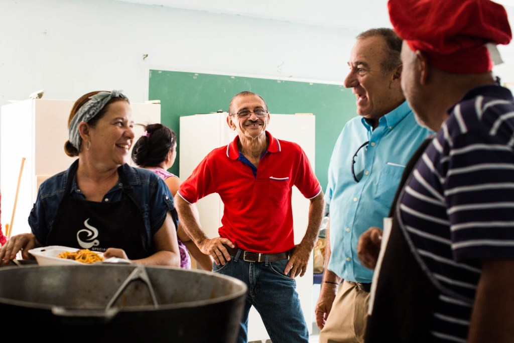(From left) Residents Evelyn Roman, Miguel Morales and Luis A. Perez (far right) talk with Manuel Cidre, from Por Los Nuestros (second from the right) in Barrio Vivi Arriba, Utuado, Puerto Rico., on June 7, 2018. Inside the former public school, a free solar-powered laundry service, funded by Direct Relief, was built for the nearby communities, who have been without power for over nine months. The former school serves as a community and aid center in the aftermath of Hurricane Maria. (Photo by Erika P. Rodríguez for Direct Relief)