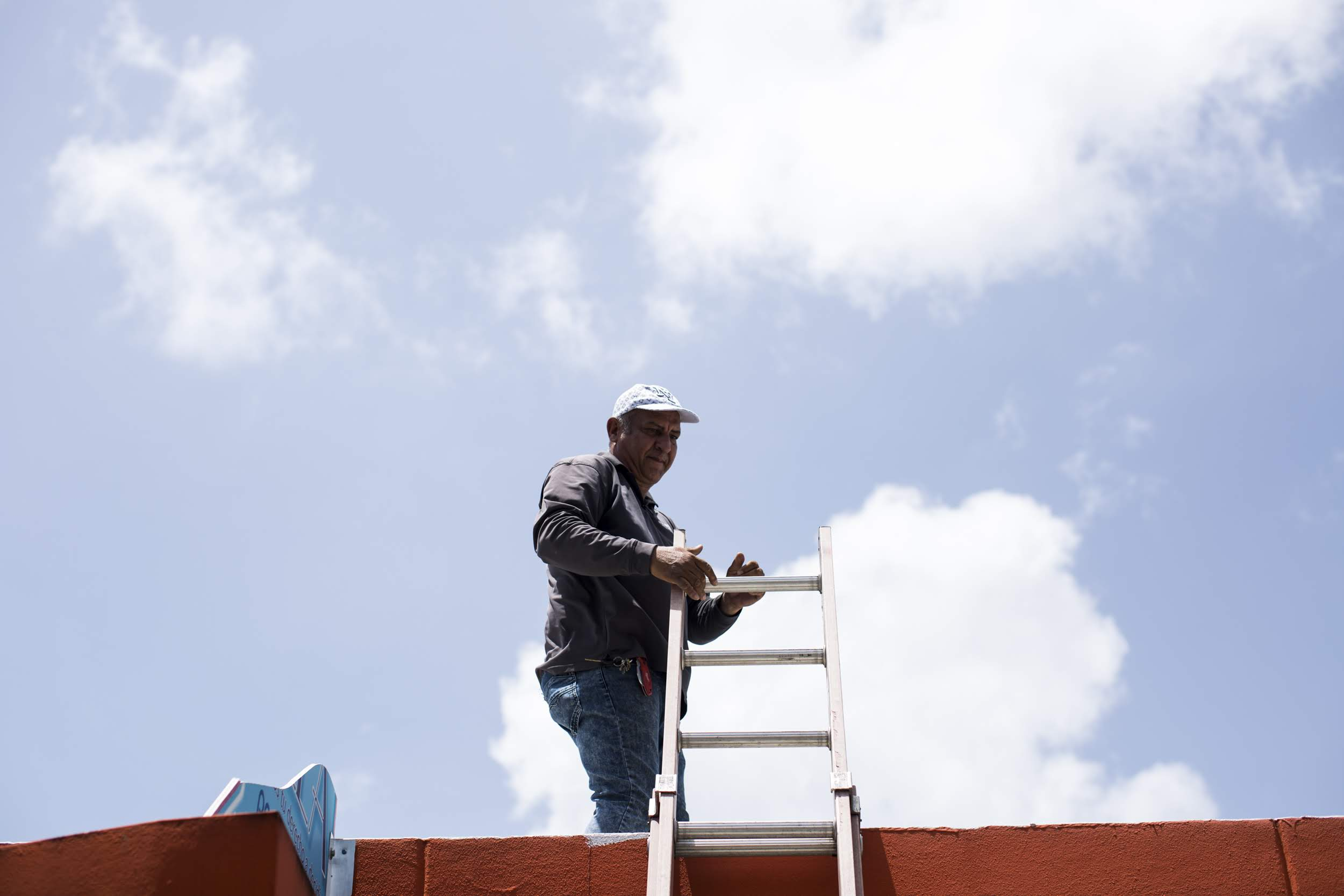 Noel Torres instala un sistema de energía solar en el techo de la Clínica Iella, en San Juan. Torres trabajó durante meses en la instalación de paneles solares en edificios de toda la isla después del paso del huracán María mientras no tenía electricidad en su propia casa. (Erika P. Rodríguez, Direct Relief)