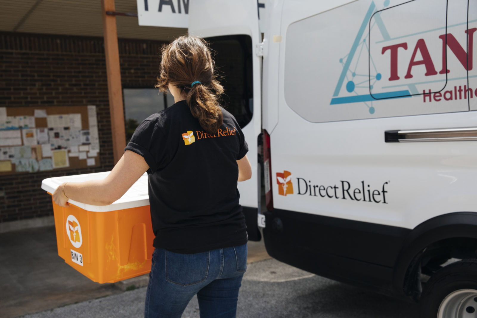 Direct Relief staff load medical supplies into a mobile clinic in Raywood, TX. After Hurricane Harvey, Direct Relief purchased the mobile clinic transport van for TAN Healthcare in Beaumont, which was seriously impacted by the hurricane. The facility has been able to expand beyond clinic walls to reach patients in rural areas. (Photo by Donnie Hedden for Direct Relief)