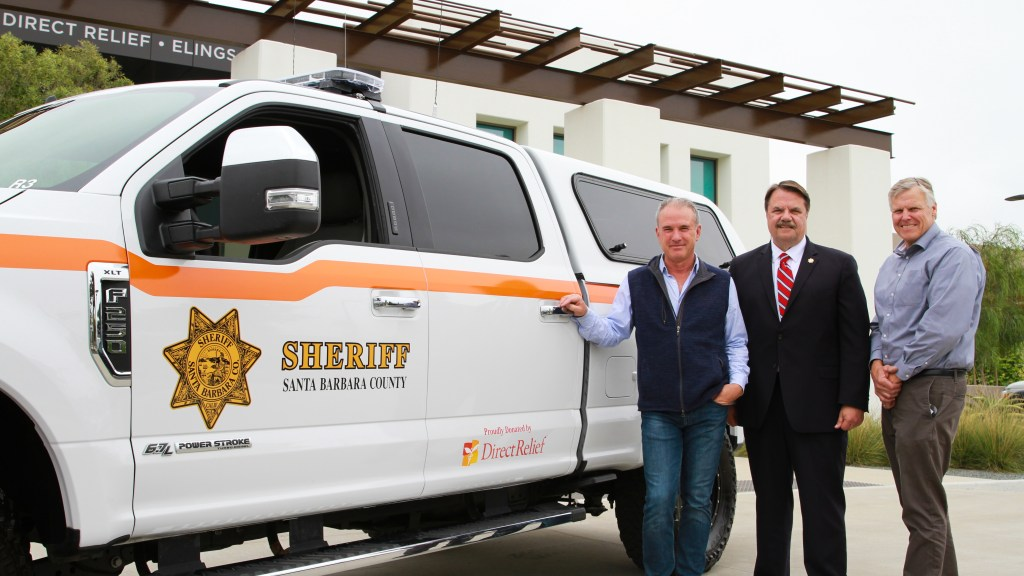 Direct Relief CEO Thomas Tighe, Santa Barbara County Sheriff Bill Brown, and SBC Search and Rescue Commander Nelson Trichler in front of the new Search vehicle. (Noah Smith/Direct Relief)