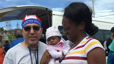 Dr. Edwin Rodriguez, a pediatric cardiologist based in Puerto Rico, with a small patient and her mother in Grand Bahama. Dr. Rodriguez traveled to the Bahamas in the wake of Hurricane Dorian with the NGO Haiti Stands Up to provide at-home care for patients too unwell or immobile to travel. (Photo courtesy of Dr. Edwin Rodriguez)