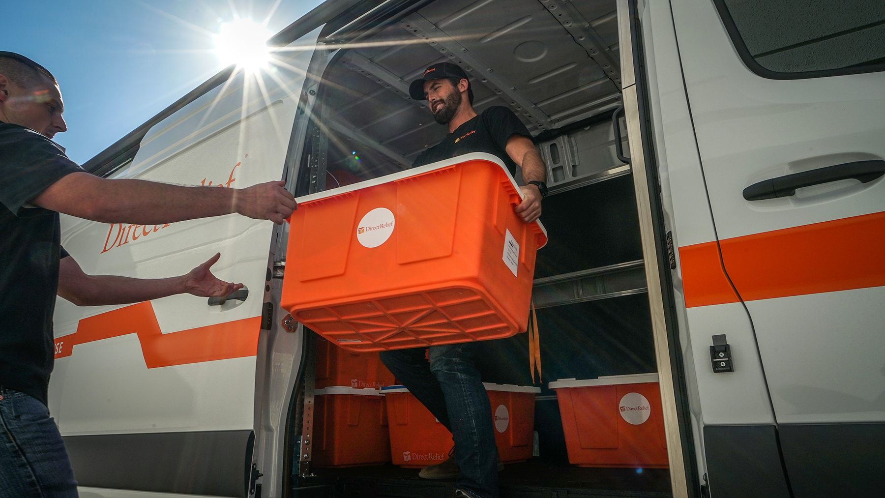 Direct Relief's emergency response team hands off medical supplies to staff at the Petaluma Health Center in response to the Kincade Fire. (Lara Cooper/Direct Relief)