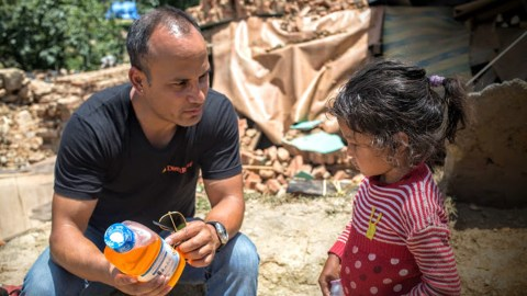 A Direct Relief staff member explains the difference between soda and Pedialyte to a child affected by the 2015 Nepal earthquake.
