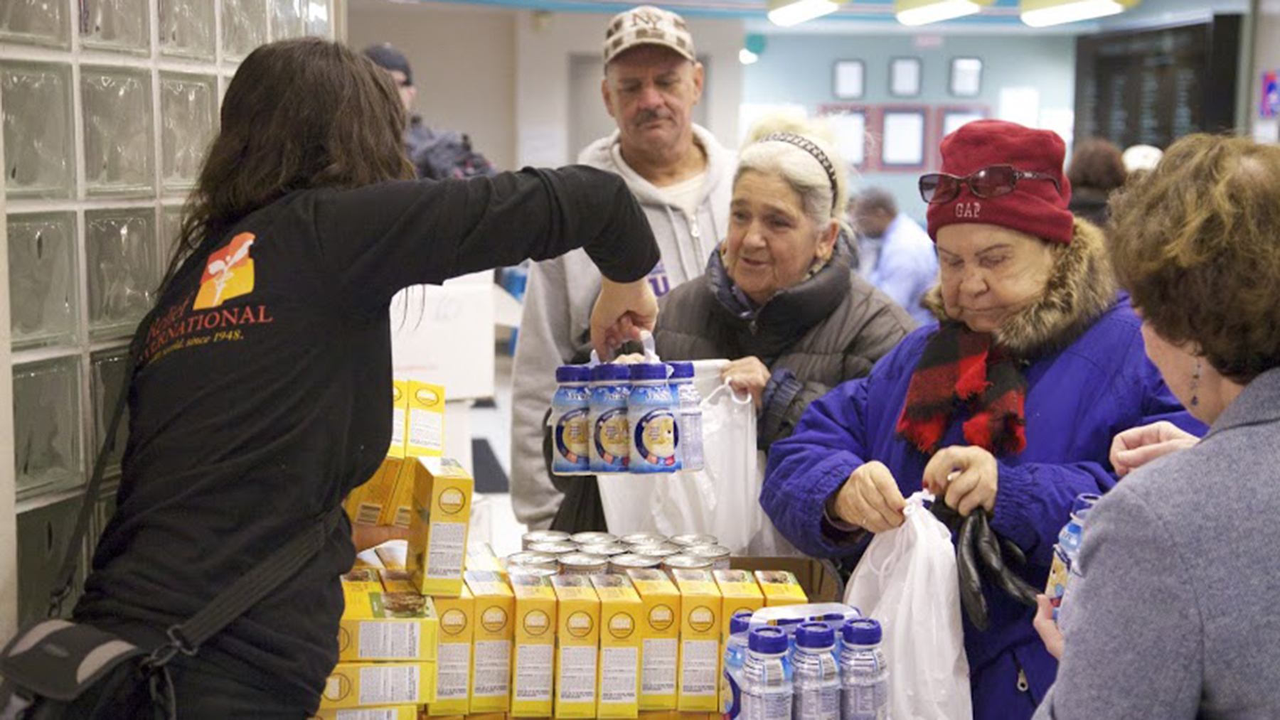 A Direct Relief staff member passes out supplies to people affected by Hurricane Sandy. (Photo by William Vazquez for Direct Relief)