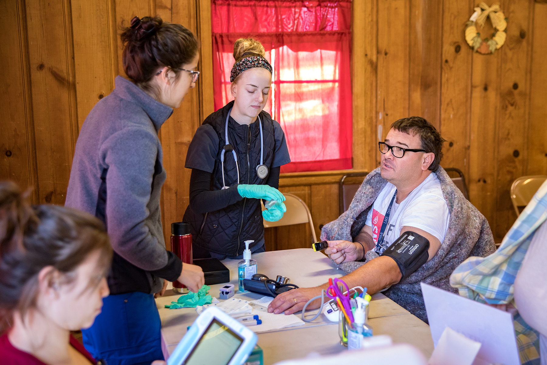 Volunteers at free clinic Medspire, take a patient's vitals during a clinic day in Magalia, California. The free clinic was started to address unmet needs of vulnerable residents after the Camp Fire destroyed most of neighboring Paradise. (Mark Semegen for Direct Relief)