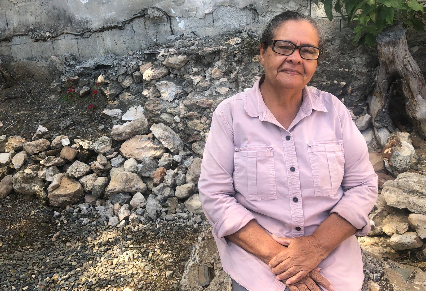 Minerva Rodriguez, a pastor in Yauco, Puerto Rico, sits in front of her church that was damaged during recent earthquakes on the island. Rodriguez was one of the community leaders that helped establish outdoor communities as aftershocks continued. (Photo by Alejandra Rosa Morales for Direct Relief)
