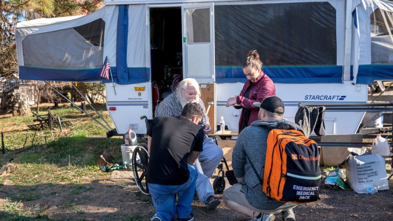 Many residents of Butte County, where the 2018 Camp Fire killed more than 80 people and displaced thousands, are still without permanent housing. Covid-19 is compounding an already challenging situation. Here, volunteers from MedSpire provide care to residents in an RV community in Butte County in Nov. 2019, prior to the Covid-19 pandemic. (Photo by Mark Semegen for Direct Relief)