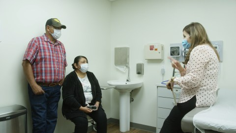 Dr. Olga Meave speaks with farmworkers and Clinica Sierra Vista patients Ramon and Laura Siordia. (Photo by Oliver Riley-Smith for Direct Relief)
