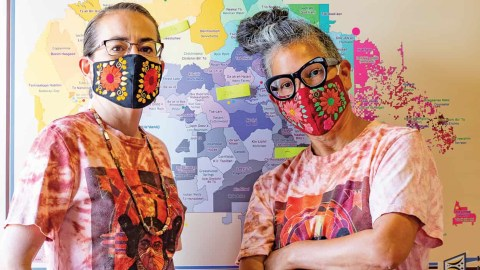 Amy Yeung (right) and Chenoa Bah in front of a map of Navajo Nation. The women are part of a collective effort to provide PPE and other needs for community members of the Nation during the Covid-19 pandemic. (Stephanie Cameron/ Courtesy of Edible New Mexico)
