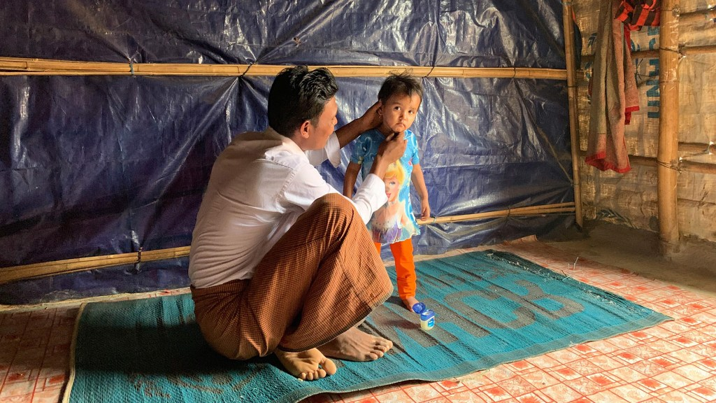 Un padre cuida la piel de su hijo en Cox's Bazar, Bangladesh.  Como parte del Vaseline Healing Project, se llevaron a cabo misiones médicas en el hospital de campaña de HOPE en Cox's Bazar, Bangladesh, para brindar atención dermatológica a los refugiados rohingya sin acceso.  (Ellen Cho / Alivio directo)