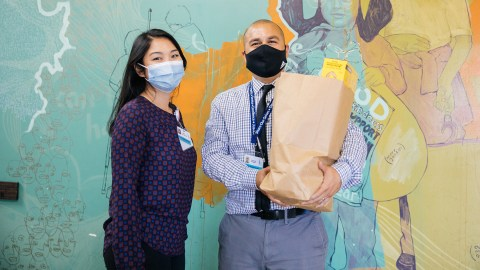 Nancy Dao, Clinical Pharmacy Manager and Fernando Gallegos, Community Health Work and Pharmacy Technology.  in the Sharing Our Selves (SOS) pantry in Costa Mesa, California.  where donated food is repackaged and served to those in need.  As the winner of the BD Helping Build Health Communities award, Share Our Selves (SOS) has strengthened its clinical pharmacy program specifically to more effectively treat chronic conditions such as diabetes and hypertension.  They used grant funds implemented by Direct Relief to hire a community health worker and pharmacy technician (Fernando Gallegos) to make home visits, dispense medications, assess social determinants of health and further develop the effectiveness of telehealth and digital literacy.  SOS is a nationally recognized health center that provides comprehensive, high quality safety services to the Orange County community.  One of 256 health centers nationwide to be designated as a homeless health care provider, SOS is a patient-centered medical home and values the concept of the right person, the right treatment, at the right time.  PHOTO: Donnie Lloyd Hedden Jr. 2021