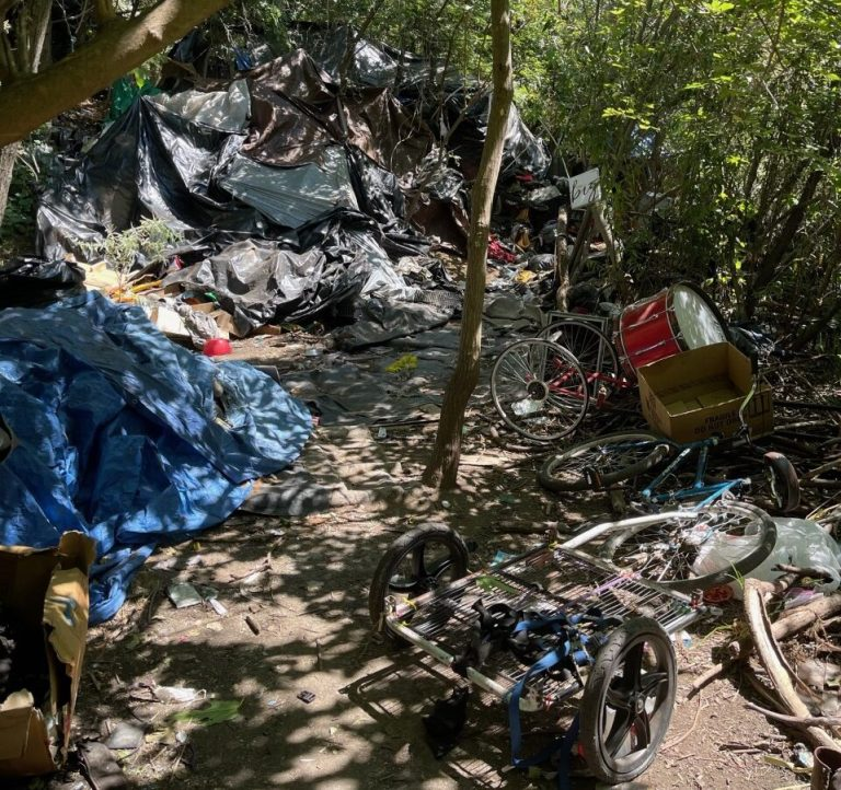"""Comanche Creek homeless encampment. In the foreground is Medspire patient Jesse Richardson's home. """"This isn't trash, this is what I have left and I live here,"""" he said. (Photo Courtesy of Natalie Soto)"""