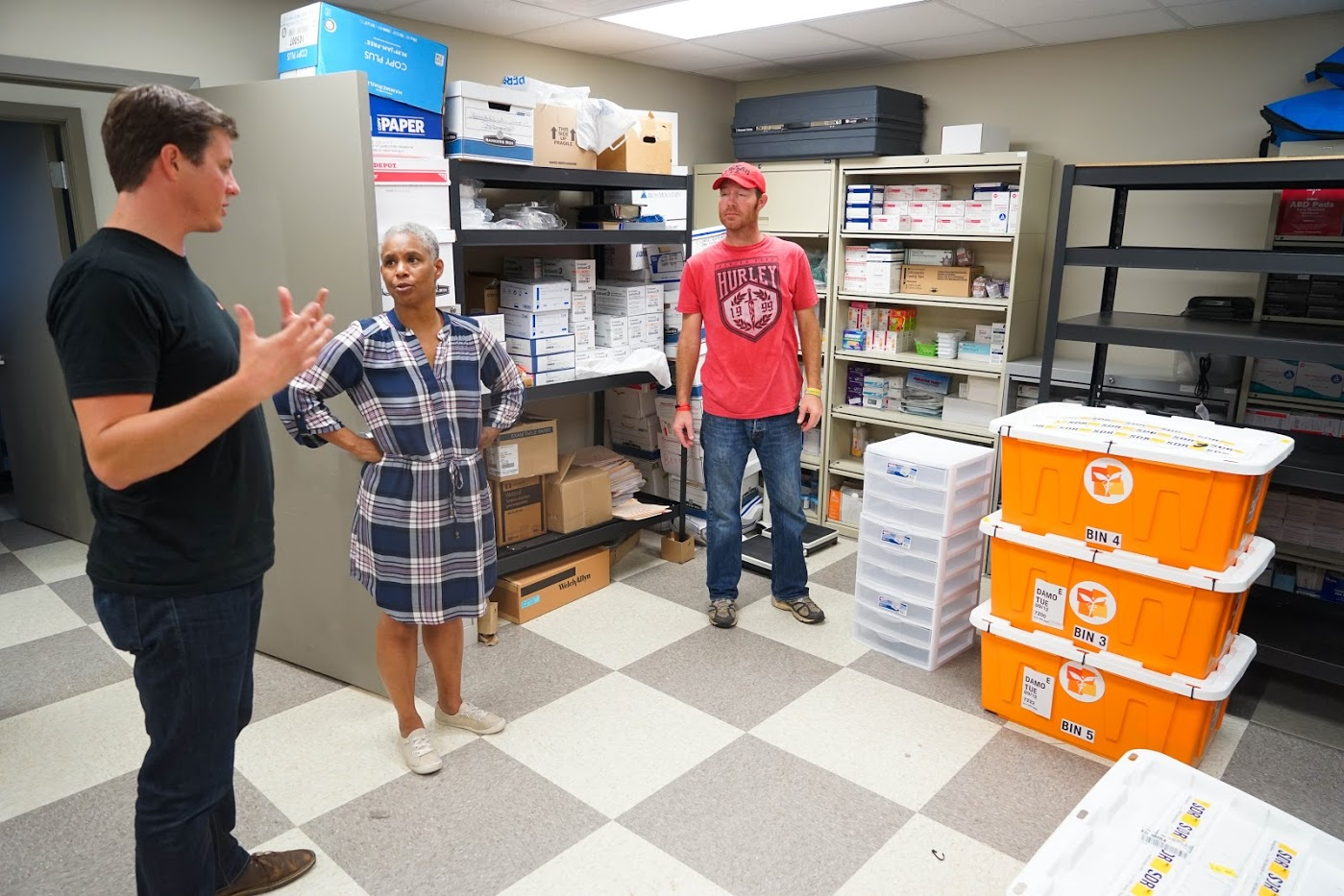 Direct Relief's Damon Taugher speaks with Triangle Area Network Director Dena Hughes at TAN's clinic in Beaumont, Texas, in 2017 after Hurricane Harvey made landfall. (Lara Cooper/Direct Relief)