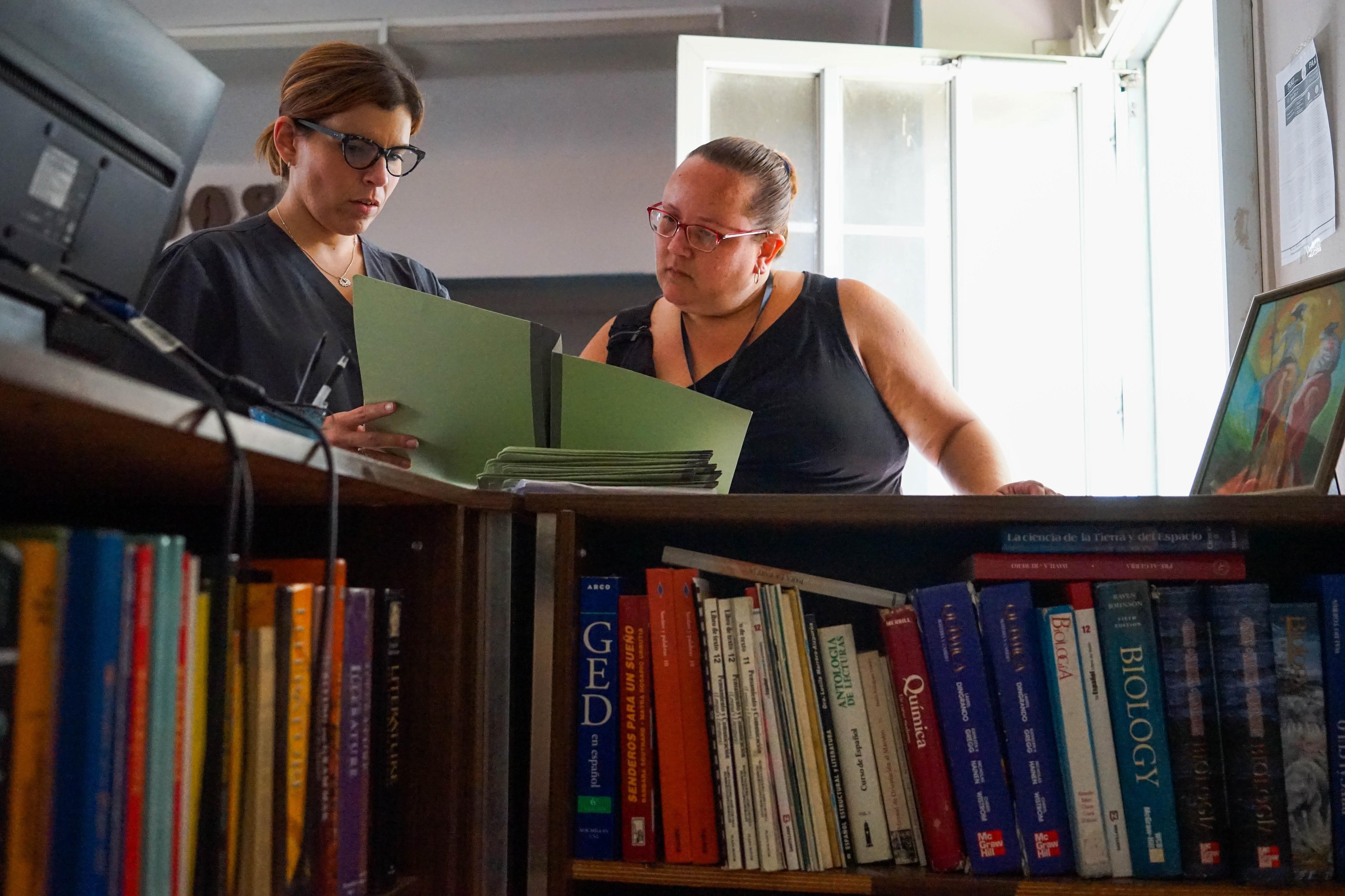 La Dra. Carla Rossotti y Lisel Vargas repasan el archivo de un paciente dentro de una biblioteca para niños que se convirtió en una clínica médica. (Lara Cooper/ Direct Relief)