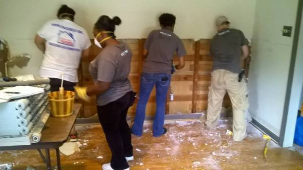 Volunteers cleaning up homes damaged from flooding wear donated N95 masks to protect them from loose debris. Photo: NACC Disaster Services.