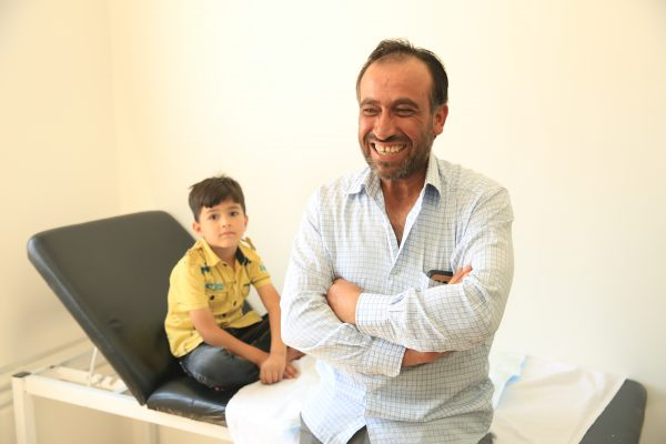A Syrian man and his son visit a free clinic in Jordan that was set up in partnership with the Vaseline Healing Project and the Jordan Health Aid Society.