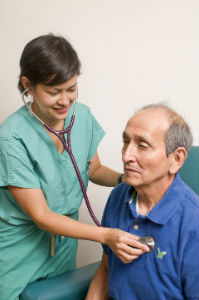 female doctor listening to older male's heart